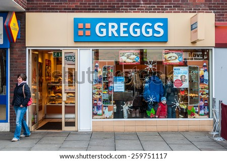 GLOUCESTER, UK - DECEMBER 04: unidentified woman leaving Greggs bakery shop on December 04, 2011 in Gloucester, UK. Founded in 1939, Greggs is the largest bakery chain in the UK with 1,671 outlets.