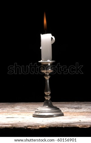 glowing candle on a table, over black