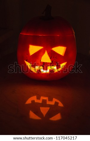 Glowing halloween pumpkin with scary face with great reflection on marble