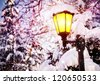 Glowing lamppost with snow and icicles in the park in Christmas time - stock photo