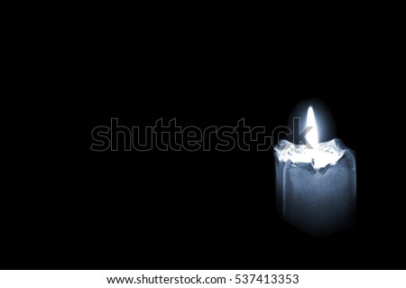 Glowing mourning candle on black background with empty space for text.