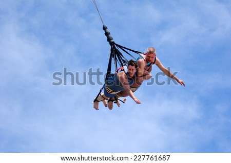 GOLD COAST, AUS - OCT 30 2014:Mature couple rids on SkyCoaster in Wet'n'Wild Gold Coast water park. In 2009, the park received 1,095,000 visitors ranking it first in Australia and eighth in the world