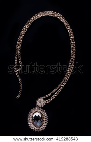 gold necklace on a black background. gems.