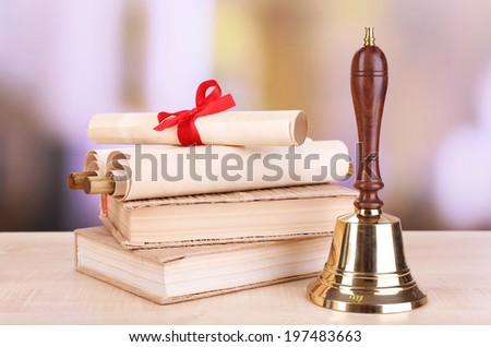 Gold retro school bell with books on table on bright background