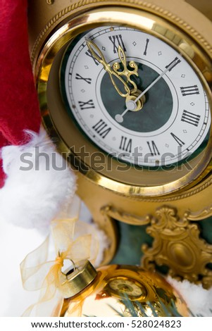 Gold retro watch with Santa Claus hat on snow and pine tree background.