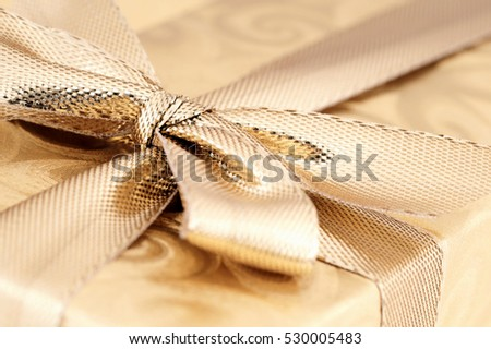 Gold wrapped gift with ribbon.