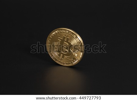 Golden Bitcoin coin on black background