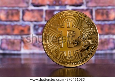 golden bitcoin on brick wall