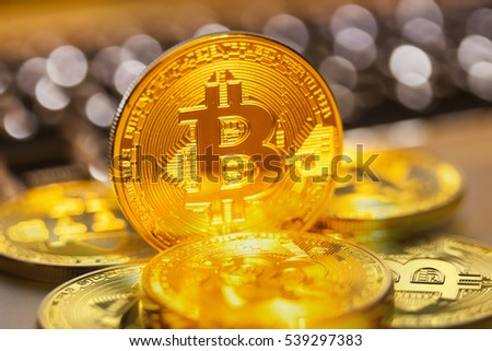 Golden Bitcoins on a laptop keyboard.Photo (new virtual money ) Soft focus