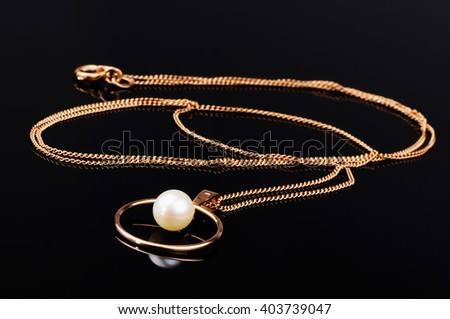 Golden chain with pendant on black mirrored surface