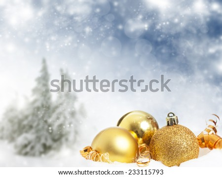 Golden Christmas decorations and gift box in the snow, snow cowered pine trees in the background