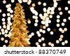 Golden Christmas tree and light out focus - stock photo