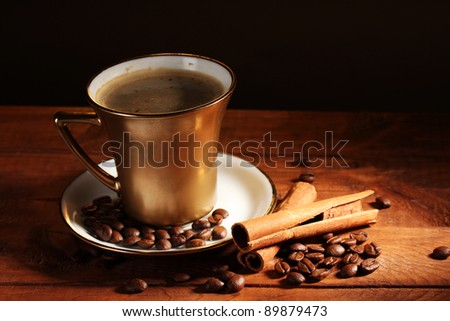 golden cup with coffee, cinnamon and coffee beans on wooden table on brown background