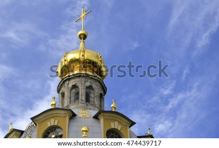 Golden dome of the temple against the blue sky with clouds