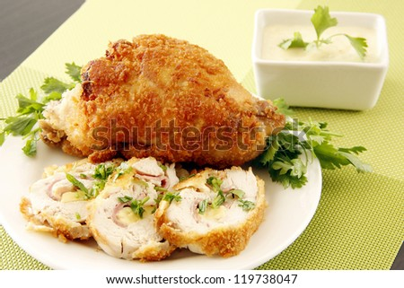 Golden fried stuffed chicken with cream and garnishing