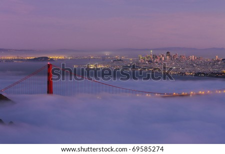 GOLDEN GATE NATIONAL RECREATION AREA, CALIFORNIA: Golden Gate Bridge taken from Hawk Hill overlook in Marin County with fog flowing over bridge at twilight.