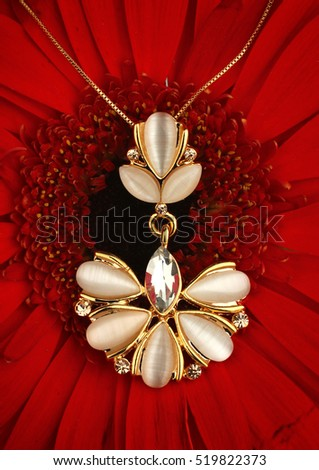 Golden jewellery pendant with nacre on flower background