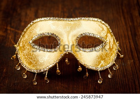Golden shiny Venice mask on rustic wooden background