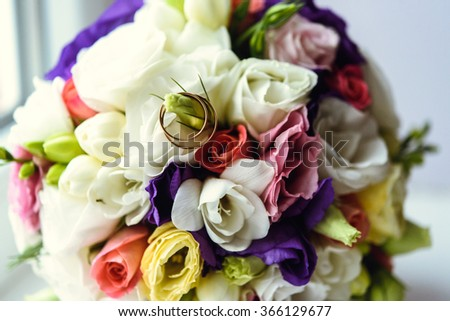golden wedding rings on beautiful colorful bridal bouquet
