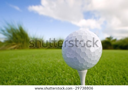 golf ball and tee on lush tropical course with copy space