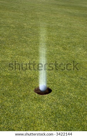 Golf Ball Landing Straight in the hole On a golf green ( hole in one)