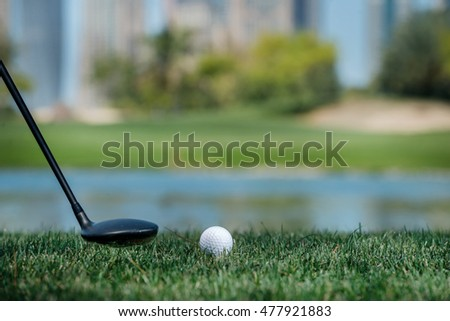 Golf ball lying on the grass in front of Dubai skyscrapers. Golf courses. Close-up view of a golf ball on green grass.