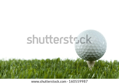 Golf ball on a tee in the grass with copy space