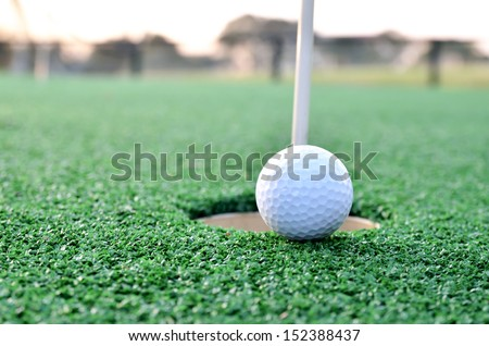 Golf ball sits at the lip of the hole on the putting green