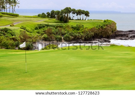 Golf course with bunker and flag. Green fields of island