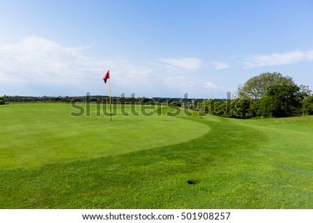 Golf Flag-Stick Green Golf hole putting green flag-stick closeup blue sky landscape