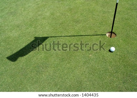 Golf green with flag and ball