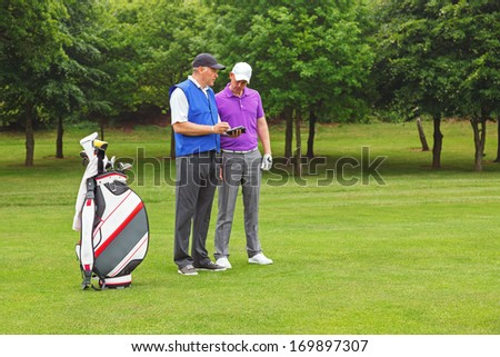 Golfer and caddy standing on the fairway of a par 4 looking at a course guide.