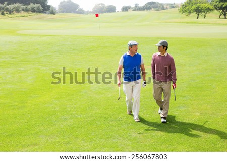 Golfer friends walking and chatting on a sunny day at the golf course