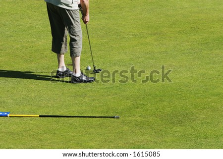golfer putting a short shot into the hole on a golfcourse