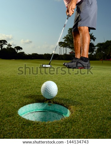 Golfer putting ball in hole on golf course