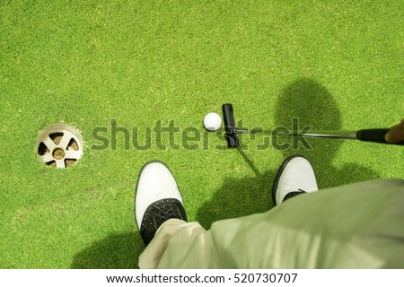 Golfer putting golf ball on the green golf.