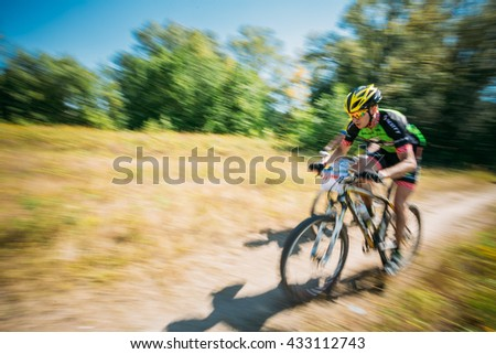 Gomel, Belarus - August 9, 2015: Mountain Bike cyclist riding track at sunny day, healthy lifestyle active athlete doing sport. Blurred motion background