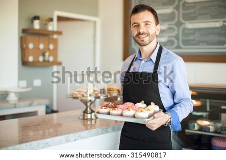 Good looking young Hispanic man holding a tray of cupcakes and greeting customers to his cake shop