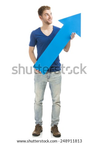 Good looking young man holding a blue arrow, isolated on a white background