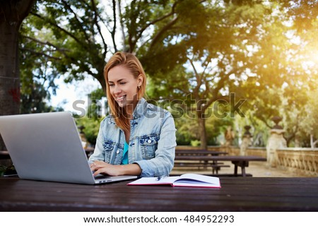 Gorgeous female student with beautiful smile is working on laptop computer, while is sitting on a university campus. Cheerful hipster girl is using portable net-book for training classes in college
