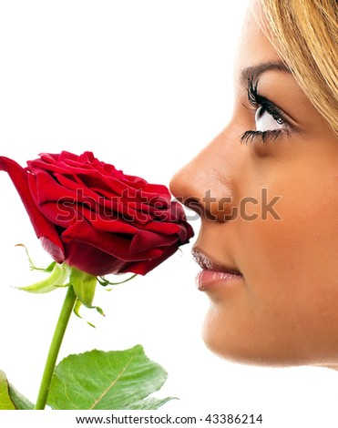 Gorgeous girl smelling the scent of a red rose