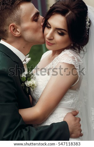 gorgeous happy bride and groom kissing. sensual tender emotional moment of luxury wedding couple in sunny outdoor