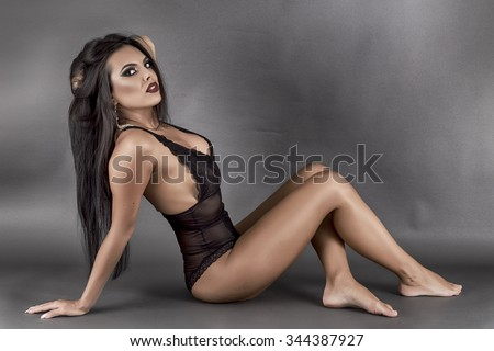 Gorgeous latin young woman posing on the floor over gray background, studio shot
