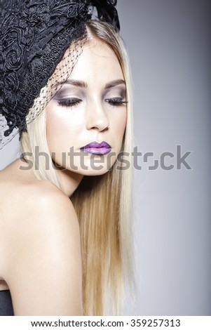 Gorgeous model  with a fashionable makeup wearing a hat decorated with veil and a strapless top