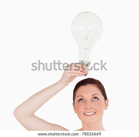 Gorgeous red-haired woman holding a bulb while standing on a white background