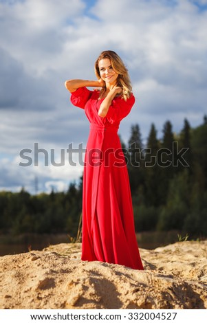 Gorgeous red head young woman in long red dress on a background of a lake. Sandy canyon. Fashion style