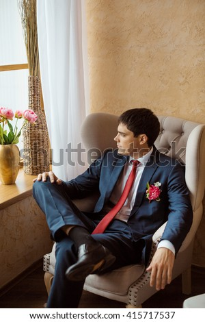 Stylish Man Posing In Chair In White Room