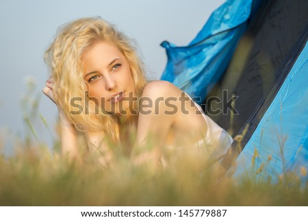 Gorgeous smiling blond woman relaxing in the entrance of a camping tent while watching the sunrise.