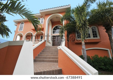 Gorgeous two-tiered stairway leading up to a magnificent Florida mansion.