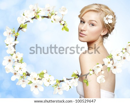 Gorgeous young blond woman with spring flower branch on bright blue background